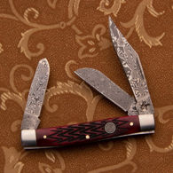 3 blades of this Roper pocket knife are 57 layer Damascus, the red jigged bone handles have a zigzag texture