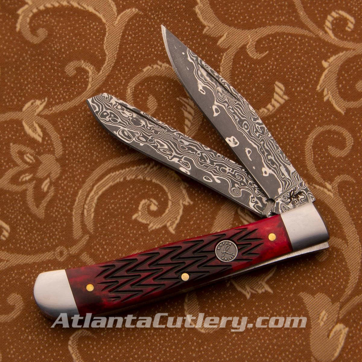 2 blades of this Roper pocket knife are 57 layer Damascus, red jigged bone handles adorned with a zigzag texture