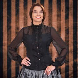 hourglass blouse has sheer shoulders and sleeves, solid midsection, and wide lace down the front, on the collar, and elastic cuffs
