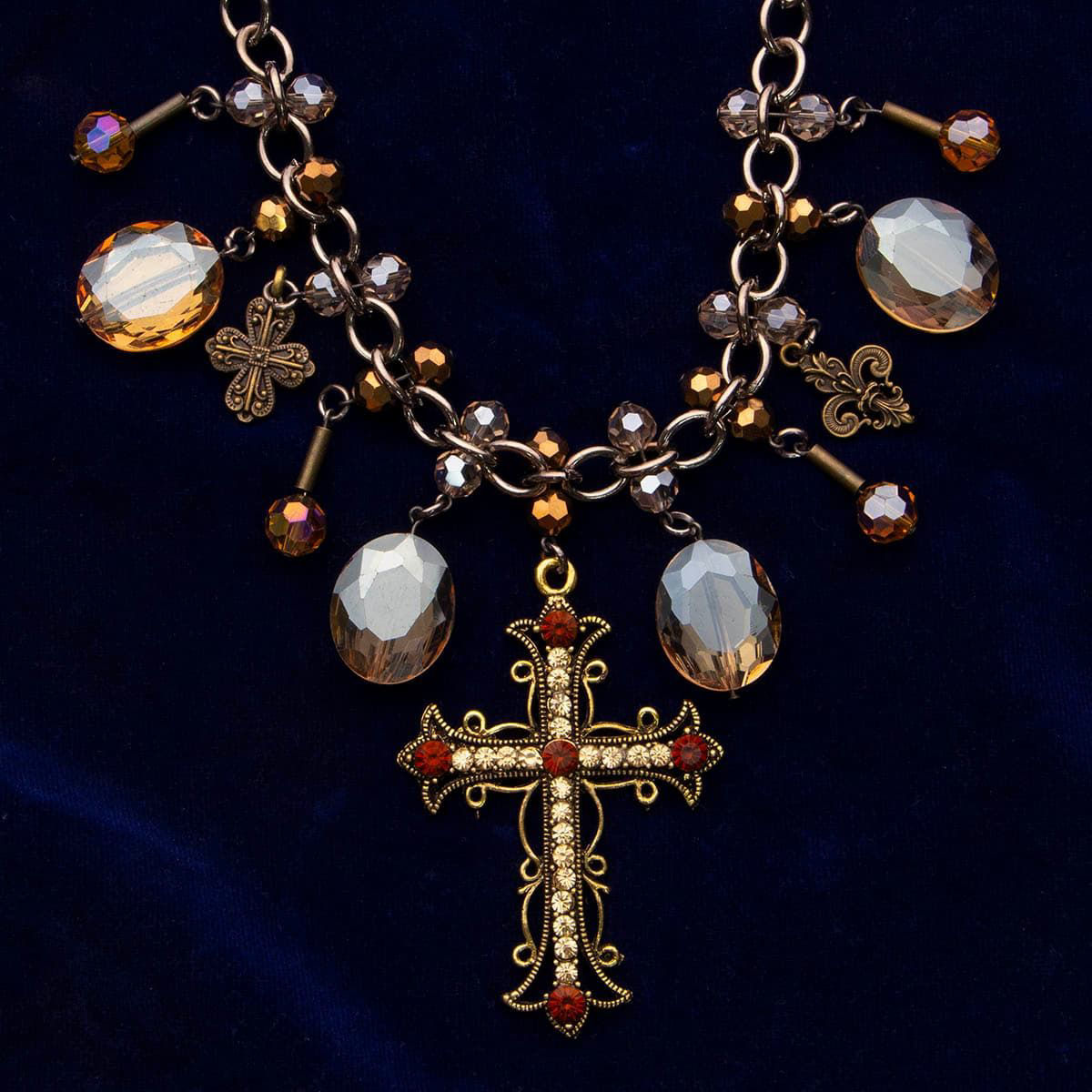 choker has faux pale topaz, fleur-de-lis and cross pendants centered by a large brass cross with faux rubies and yellow diamonds