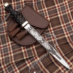 Scottish dirk has sharp 1055 high carbon steel blade etched on both sides with foliage and thistle motif, includes leather sheath